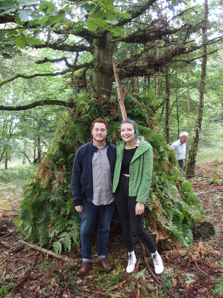 woodland den with couple in front